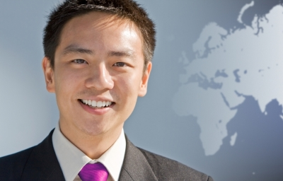 smart young Asian businessman standing in front of world map