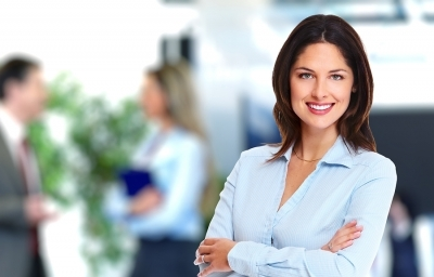 Attractive manager stands crossed armed in her office smiling at camera