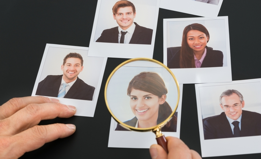photos of business people, one image, that of a woman in spotlighted under a magnifying glass