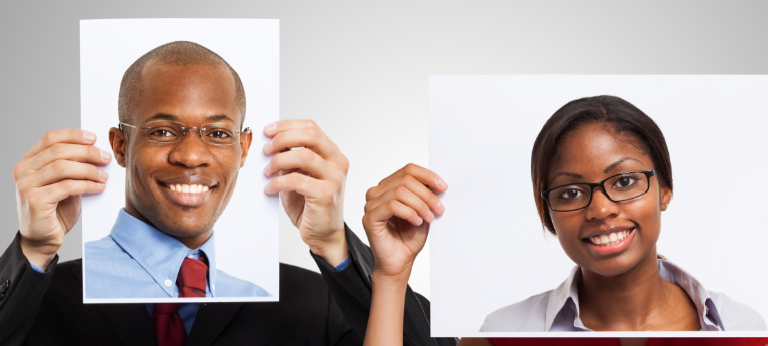 business pair holding photos of themselves in front of their faces