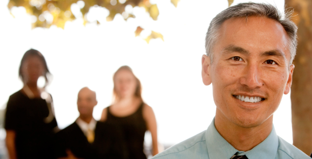 attractive asian businessman with team in background